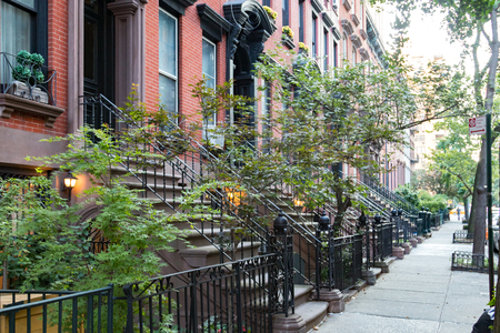 Empty sidewalk in front of historic brownstone buildings in Manhattan New York City NYC