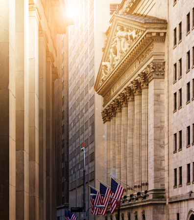 New York City historic buildings of the financial district in lower Manhattan near Wall Street with sunlight glowing in the background Stock Photo