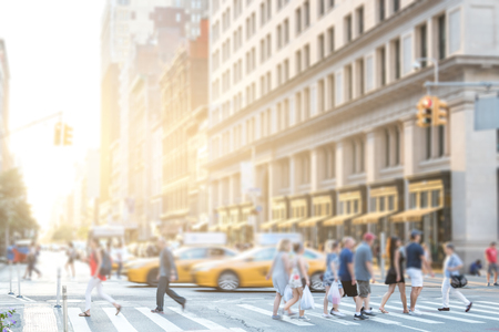 Crowds of anonymous people walking across an intersection on 5th Avenue in Manhattan New York City with colorful sunlight background