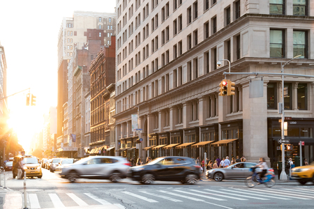 NEW YORK CITY - JUNE, 2018: Cars speed down 5th Avenue with the glow of sunlight reflecting on the background buildings in Manhattan.