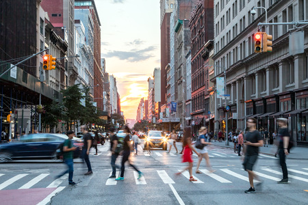 NEW YORK CITY - JULY, 2018: Intersection of 23rd Street and 5th Avenue is busy with people and cars and the colorful light of sunset in the background of the Manhattan skyline. Editorial