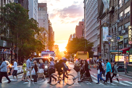 NEW YORK CITY - JUNE, 2018: Crowds of people cross a busy intersection on 23rd Street and 6th Avenue in Manhattan with a colorful sunset in the background skyline