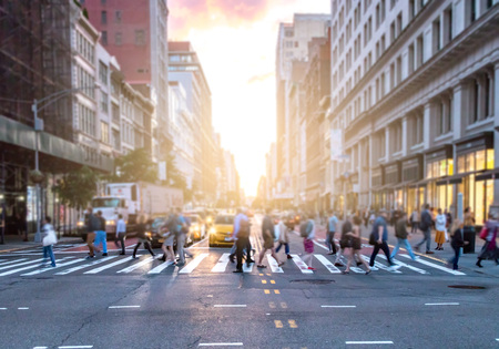 Busy intersection of 23rd Street and 5th Avenue in Manhattan with crowds of diverse people crossing in front of cars and taxis in New York City Imagens