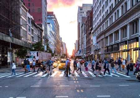 NEW YORK CITY - JUNE, 2018: Crowds of diverse people cross the busy intersection on 23rd Street and 5th Avenue in Manhattan with rush hour traffic in the background.