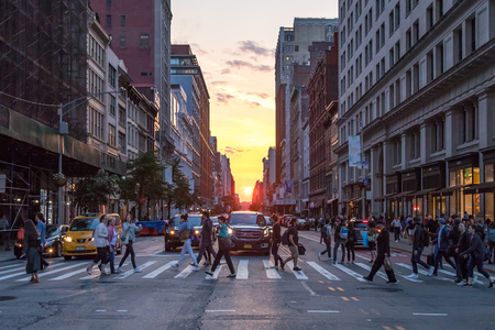 NEW YORK CITY - JUNE 7, 2018: The intersection of 23rd Street and Broadway is crowded with busy people and cars as the sun sets between the buildings of Manhattan in the background. Sajtókép