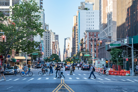 NEW YORK CITY - CIRCA 2018: Crowds of people walk across the busy intersections on 3rd Avenue in the East Village neighborhood of Manhattan in NYC