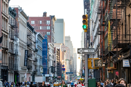 NEW YORK CITY, CIRCA 2018: Intersection of Broadway and Spring Street is busy with crowds of people walking the sidewalks in SoHo Manhattan, New York City NYC.