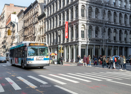 NEW YORK CITY, CIRCA 2018: A city bus drives through the busy intersection of Broadway and Broome Street in the Soho neighborhood of Manhattan NYC.