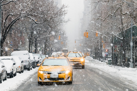 Taxis drive down a snow covered 5th Avenue during a winter nor'easter storm in Manhattan, New York City Stock fotó