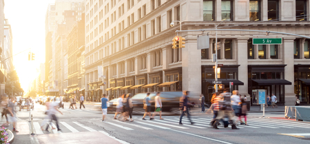 New York City street scene with crowds of people walking in Midtown Manhattan and sunlight background 免版税图像