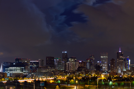 Denver Colorado downtown city skyline at night with clouds overhead