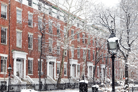 Snow covered winter street scene with old buildings along Washington Square Park in Manhattan New York City NYC 免版税图像