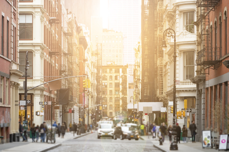Busy intersection of Broome and Greene Streets is crowded with people and cars in the SoHo neighborhood of New York City with sunlight background Imagens