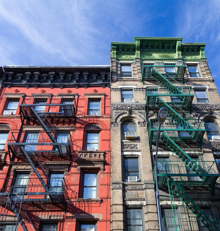 Colorful old historic apartment buildings with fire escapes in Manhattan New York City NYC