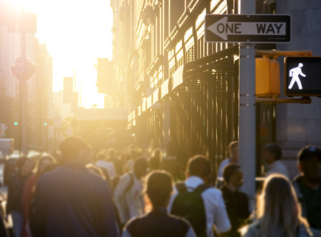 Crowd of anonymous people walking down the sidewalk with bright sunlight in the background on a busy street in Midtown Manhattan, New York City NYC