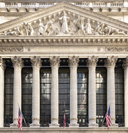 NEW YORK CITY - CIRCA 2019: American flags hang above the entrance of the historic New York Stock Exchange building in the financial district of Manhattan.