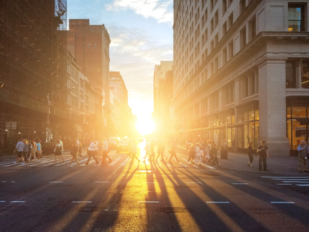 View of a busy intersection on 23rd Street in Manhattan with sunlight shining on crowds of people in New York City
