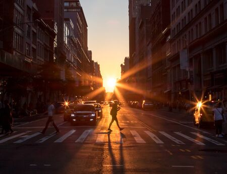 Sunlight shines on a woman crossing the intersection with a long shadow cast on the streets of Midtown Manhattan in New York City NYC