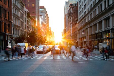 Crowds of busy people walking through the intersection of 5th Avenue and 23rd Street in Manhattan, New York City with bright sunset background 版權商用圖片