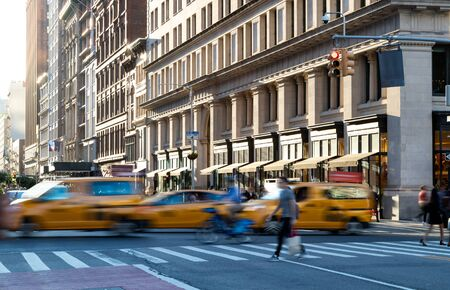 Yellow taxis in motion driving down 5th Avenue through Midtown Manhattan New York City with sunlight background