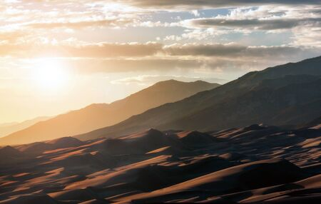 Sunlight shining over Great Sand Dunes National Park in the Colorado Rocky Mountains landscape scene 스톡 콘텐츠