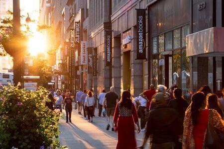 CIUDAD DE NUEVA YORK 2019: La luz del sol brilla sobre diversos grupos de personas mientras pasan por las tiendas y almacenes en las aceras de 34th Street en Manhattan, Nueva York. Foto de archivo