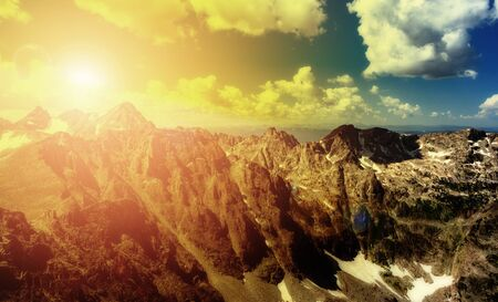 Sunlight shining over jagged mountain peaks in a colorful Colorado landscape scene
