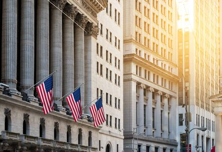 American flags flying in front of the historic buildings of Wall Street in the financial district of Manhattan, New York City NYC