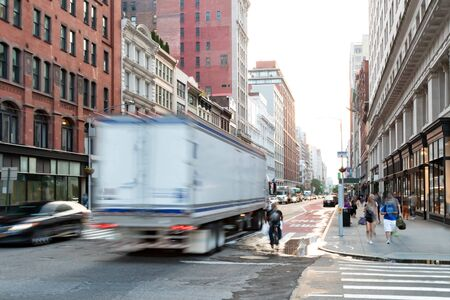 Busy view of 23rd Street with delivery truck speeding past the people walk down the sidewalk in Midtown Manhattan, New York City NYC Stock fotó
