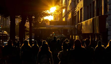 Silhouettes of people are illuminated by the bright light of sunset on the sidewalks of New York City NYC