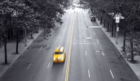 Yellow taxi speeding down 42nd Street through a black and white Midtown Manhattan cityscape in New York City NYC