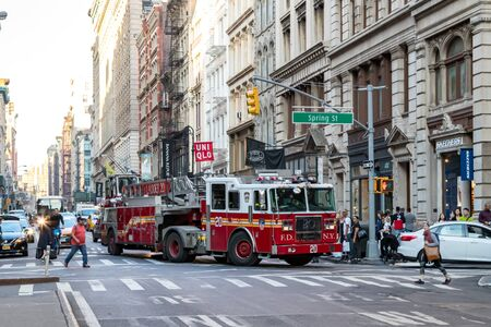NEW YORK CITY, CIRCA 2019: FDNY Firetruck turning through the crowds of people in a busy intersection in the SoHo neighborhood of Manhattan, NYC.