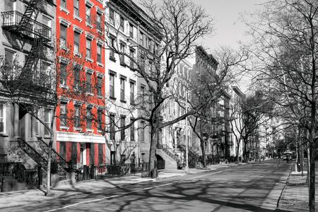Red brick building highlighted on a block of old black and white buildings in the East Village of Manhattan, New York City NYC