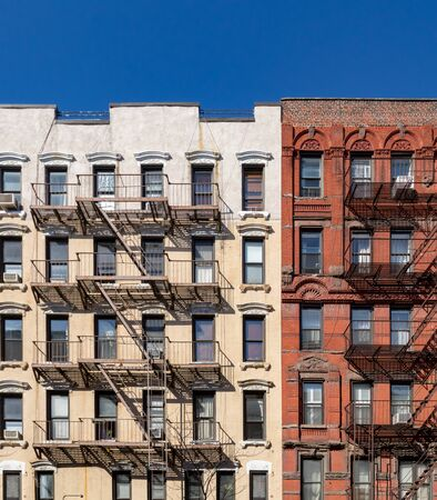 Fire escapes on the exterior of old buildings in New York City with blue sky above Reklamní fotografie