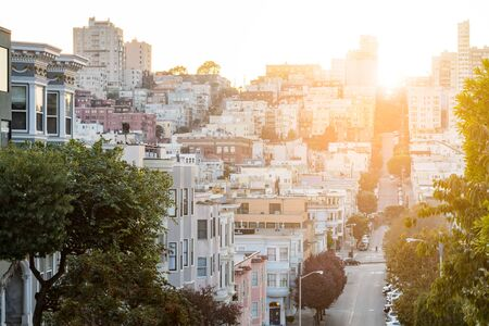 Street scene in downtown San Francisco California with the warm light of sunset shining over the crowded buildings