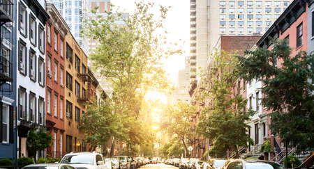 Block of historic buildings along a tree lined street in Midtown Manhattan, New York City with sunlight background