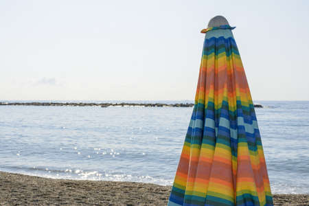relaxing day at the beach under the colorful beach umbrella by the sea Stock Photo