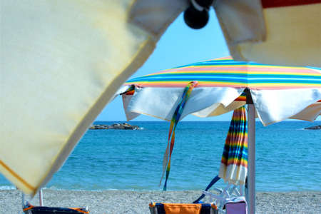 relaxing day at the beach under the colorful beach umbrella by the sea Zdjęcie Seryjne