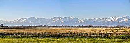 landscape of the Italian countryside of the Po valley, Novara and Vercelli with the background of the mountain range of the Alps Imagens