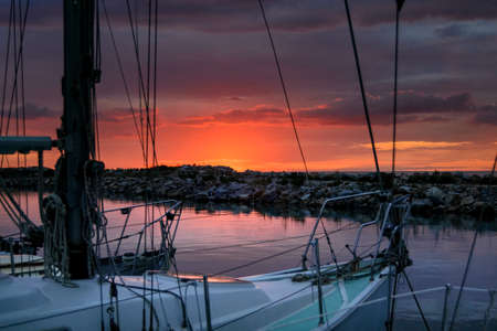 beautiful sunset over the sea, behind the cliffs, in a quiet summer evening relaxing in the harbor between the sailboats Stock Photo