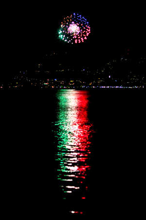 spectacular reflection of a fireworks reproducing the colors of the Italian flag reflecting the light on the sea Stock Photo
