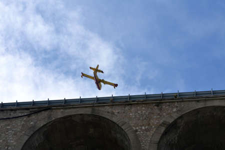 precious intervention of firefighters with a canadair flying between wood and sea to extinguish a fire, flying on a bridge
