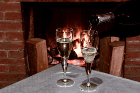 two glasses of champagne in front of the burning fireplace to celebrate a romantic evening with sweetheart