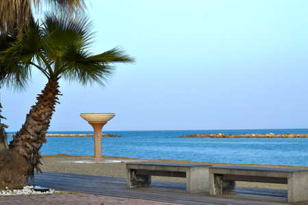 walk by the sea with palm trees, benches and a public shower on the free beach