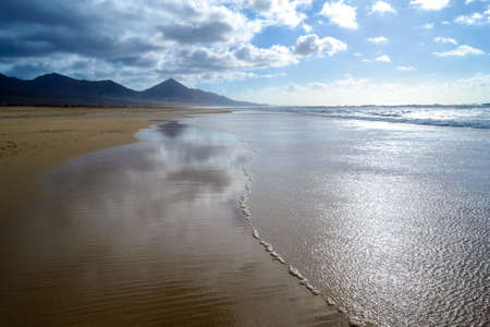 sway: magical beach of Cofete, huge expanse of sand and crystalline sea, with ocean waves, Fuerteventura, Canary Islands, Spain