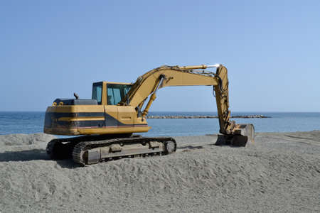 excavator working on the beach to smooth sand before summer season