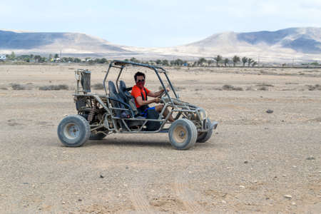 buggy racing on the sand road doing derapage at full speed amidst the desert of Fuerteventura, Canary