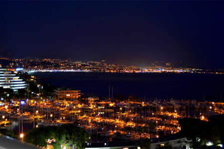 Port lights of Marina Baie Des Anges, on background the lights of Nice city reflected on the sea, during a wonderful night spent on the balcony of a residence apartment, Villeneuve Loubet, French Riviera, France Reklamní fotografie