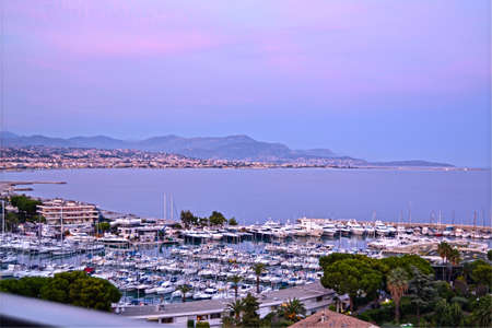 sea view and clear lights of sunrise on the port of  Marina Baie Des Anges residential center, where sailboats and yachts are moored, and on background lights of the city and the airport of Nice, Villeneuve Loubet, Cote dAzur, France