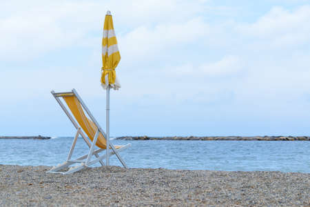 sun lounger and beach umbrella, yellow, by the sea, during a quiet summer evening Banque d'images - 95800809